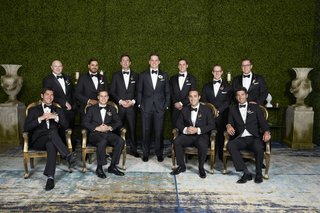 groom-in-j-hilburn-tuxedo-with-groomsmen-in-front-of-wall-of-greenery