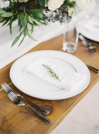 white-china-plate-on-wood-table-sprig-of-fresh-rosemary-on-napkin-on-plate-silver-flatware