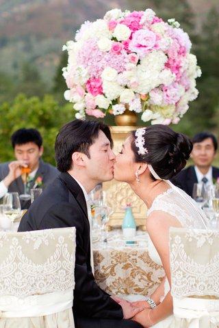groom-in-vera-wang-in-black-suit-kisses-bride-in-vera-wang-sleeveless-gown-jeweled-headband