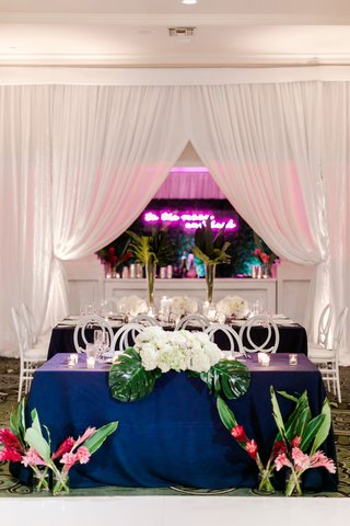 wedding-reception-sweetheart-table-navy-blue-linens-pink-tropical-flowers-greenery-palms-neon-sign
