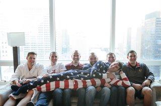 veteran-groom-in-american-flag-onesie-lounges-on-his-groomsmen