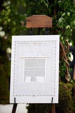 wedding-ceremony-jewish-wedding-traditions-ketubah-marriage-contract-on-easel-wood-greenery