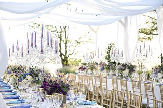 outdoor-wedding-reception-setting-with-purple-tapered-candles-and-crystal-candelabra