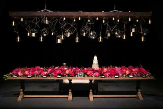 wooden-table-with-long-pink-floral-arrangement-under-unique-geometric-lighting-concept-bulbs