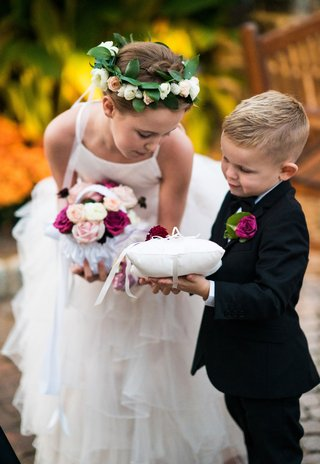 flower-girl-in-ruffle-skirt-with-basket-pink-flowers-and-flower-crown-greenery-helping-ring-bearer