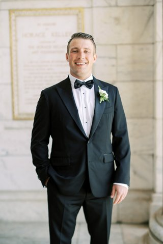 groom-in-icon-custom-suit-tuxedo-black-button-and-bow-tie-ivory-boutonniere-cleveland-wedding