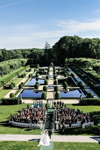 wedding-processional-bride-walking-down-aisle-with-father-oheka-castle-outdoor-ceremony-gardens