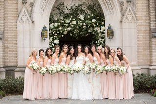 wedding-party-bridesmaids-in-strapless-pink-dresses-neutral-bouquet-in-front-of-ceremony-arch