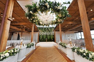 wedding-ceremony-wood-floor-aisle-white-boxes-greenery-white-flowers-beams-wreath-chandelier