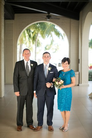 mother-of-the-groom-in-blue-teal-lace-scallop-dress-with-short-sleeves-below-the-knee-hem-bouquet