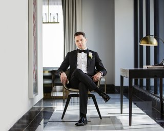 groom-in-black-tuxedo-and-bow-tie-sitting-in-chair