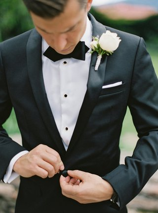 groom-in-calvin-klein-suit-with-bow-tie-white-pocket-square-and-white-rose-boutonniere-buttoning