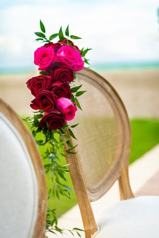 wedding-ceremony-chair-white-cushion-wood-cane-back-pink-red-roses-greenery