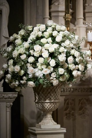 wedding-ceremony-stone-urn-filled-with-white-flowers-and-greenery-at-altar