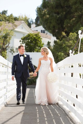 bride-in-strapless-wedding-dress-holding-groom-hand-on-bridge-in-california-holding-round-bouquet