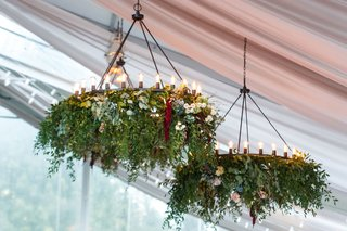 tent-wedding-reception-iron-chandelier-decorated-with-greenery-and-blooms-in-blue-red-pink