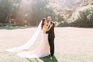 bride-and-groom-at-calamigos-ranch-wedding-venue-in-malibu-calla-blanche-wedding-dress-veil-sunlight
