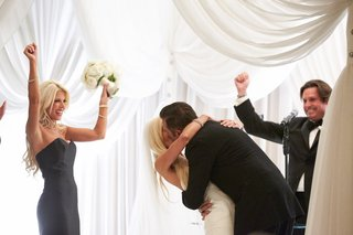 maid-of-honor-and-best-man-celebrate-during-bride-and-grooms-first-kiss