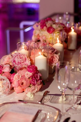 low-bundles-of-pink-flowers-and-white-pillar-candles