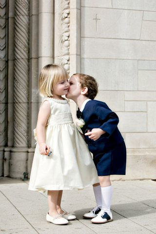 ring-bearer-in-short-suit-with-bow-tie-and-knee-socks-kiss-flower-girl-on-cheek-in-ivory-dress-flats