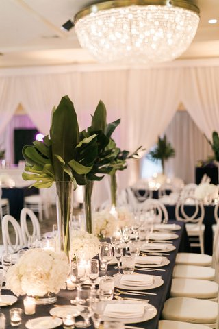 wedding-reception-chandelier-rectangle-table-navy-blue-white-hydrangea-low-centerpiece-tall-tropical