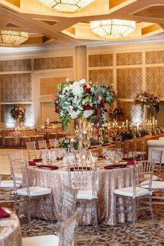 wedding-reception-gold-ballroom-round-table-burgundy-napkin-tall-centerpieces-nuage-designs
