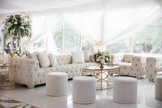 wedding-reception-chesterfield-tufted-sofa-and-armchair-ottoman-gold-table-white-decorations