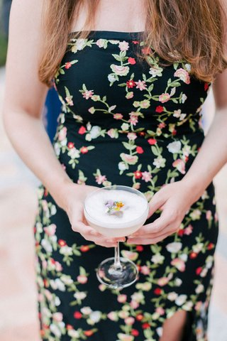wedding-guest-in-floral-print-dress-holding-coupe-glass-with-cocktail-ice-cube-and-edible-flowers
