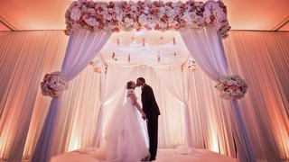 bride-and-groom-kiss-and-hold-hands-under-ceremony-altar