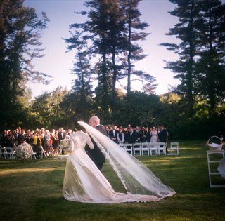 bride-with-long-veil-enters-outdoor-ceremony
