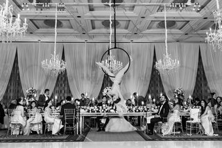 black-and-white-photo-of-aerialist-over-head-table-amongst-chandeliers-and-reception-decorations