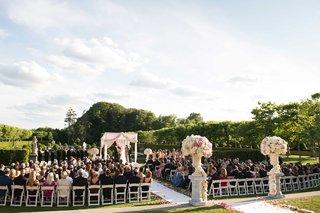 wedding-ceremony-at-oheka-castle-with-white-and-pink-flower-arrangements-pink-rose-petals-aisle