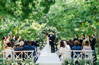 vineyard-guest-chairs-at-outdoor-ceremony-among-greenery-trees-white-flowers-white-aisle-runner