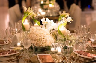 round-table-with-low-arrangements-of-white-roses-orchids-and-calla-lilies-wrapped-pillar-candles