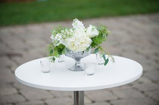 wedding-cocktail-hour-table-with-white-hydrangeas-roses-greenery-in-mercury-glass-vase-candles