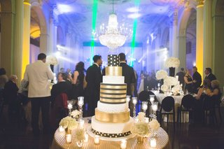 new-years-eve-wedding-cake-with-gold-stripes-and-polka-dots-under-chandelier-nye