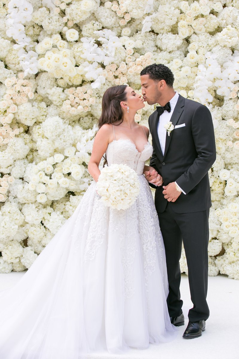 Newlyweds Kiss in Front of Floral Wall