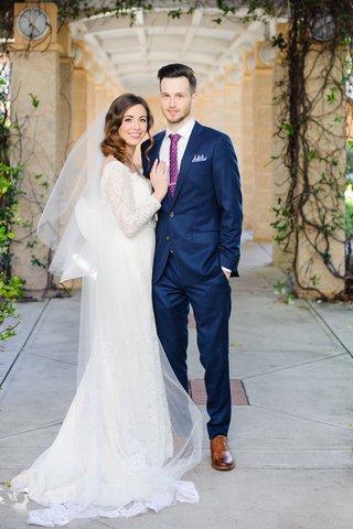 newlyweds-in-wedding-attire-under-atrium