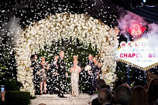 couple-at-wedding-ceremony-vow-renewal-white-flower-chuppah-chapel-of-the-bells-las-vegas-sign-elope