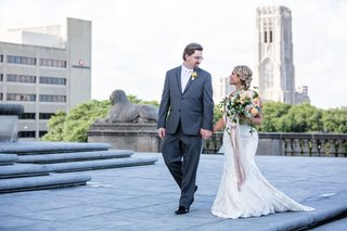 bride-in-lace-wedding-dress-with-big-bouquet-colorful-groom-in-grey-suit-in-indiana-wedding-venue