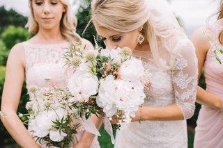 bride-in-oleg-cassini-long-sleeved-wedding-dress-smelling-bouquet