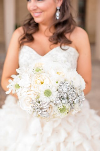bride-in-ruffle-wedding-dress-holding-white-bouquet-with-brooches