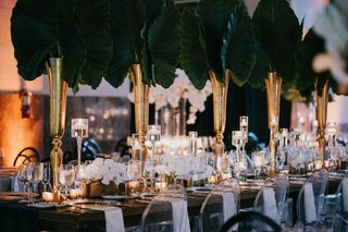 wedding-reception-table-decor-ghost-chair-white-napkin-green-linen-elephant-ear-tropical-greenery