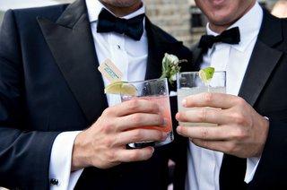 groomsmen-male-wedding-guest-cheers-holding-cocktails-in-tumbler-glasses-limes-custom-stir-sticks