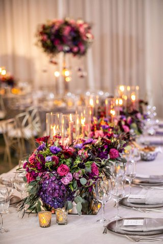 purple-pink-red-flowers-greenery-mirror-box-taper-candles-low-centerpiece-ideas