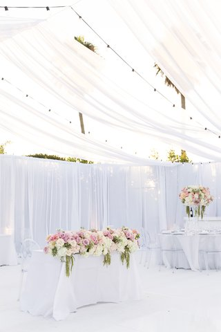tented-reception-white-space-sweetheart-table-fully-covered-with-flowers