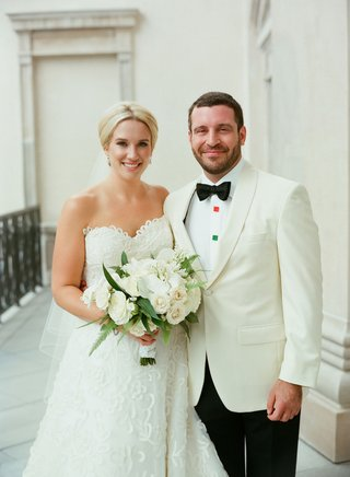 bride-in-strapless-oscar-de-la-renta-wedding-dress-white-bouquet-updo-hair-up-groom-in-white-tuxedo