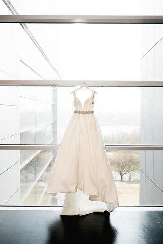 clinton-library-wedding-dress-hanging-up-on-window-ball-gown-deep-neckline-crystal-belt-sash-train