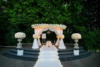 outdoor-ceremony-with-stone-platform-and-white-chuppah-with-flowers