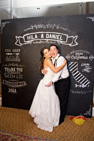 bride-and-groom-hugging-photobooth-chalkboard-design-step-and-repeat
